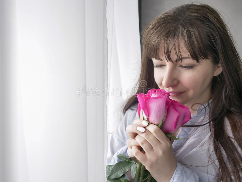 Young brunette woman sniffs a bouquet of roses standing by the window. Young woman sniffs a bouquet of roses standing by the window stock photography