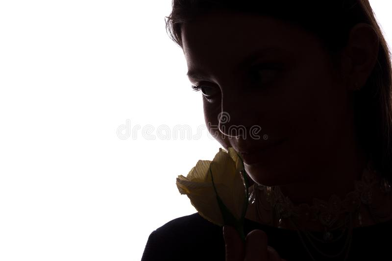 Young woman sniffs a flower - horizontal side view silhouette royalty free stock image