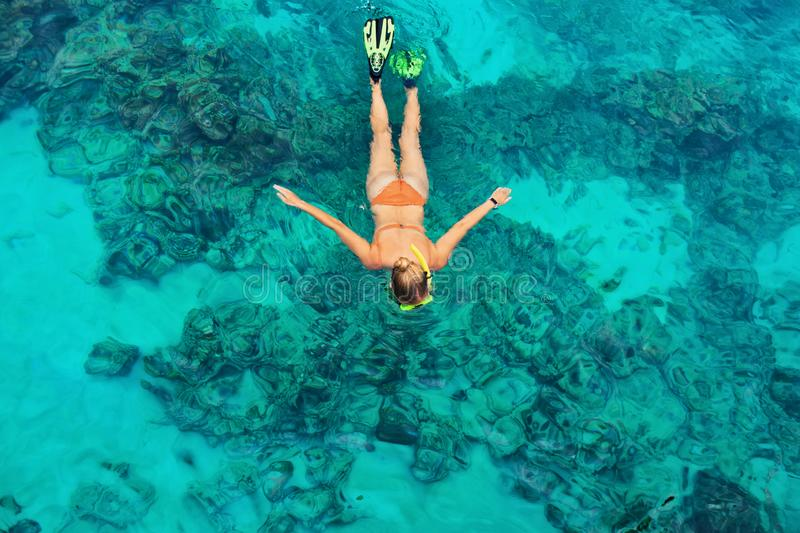 Young woman snorkeling with coral reef fishes. Happy girl in snorkeling mask dive underwater with tropical fishes in coral reef sea pool. Travel lifestyle, water royalty free stock photos