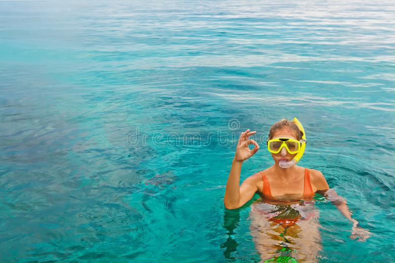 Young woman in snorkeling mask showing divers sign OK. Young woman in snorkeling mask dive underwater with tropical fishes in coral reef sea pool. Show by hands royalty free stock image
