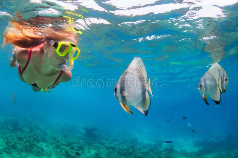 Young woman in snorkeling mask dive underwater with tropical fishes. Happy family - active woman in snorkeling mask dive underwater, see tropical fishes in coral royalty free stock images