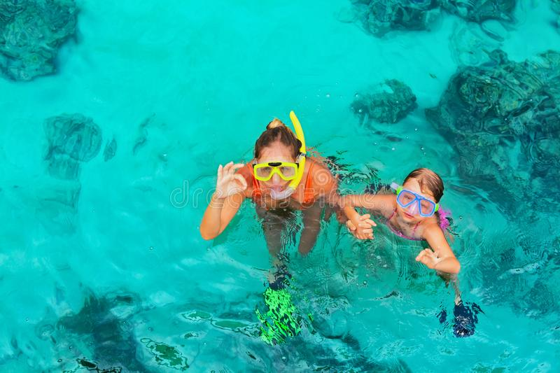 Young woman in snorkeling mask showing divers sign OK. Woman with child in snorkeling mask dive underwater with fishes in tropical sea pool. Show by hands divers royalty free stock photography