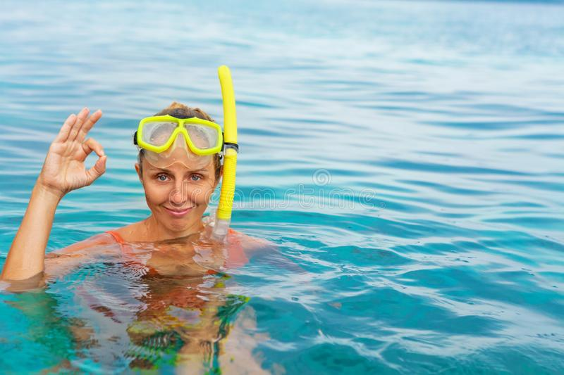 Young woman in snorkeling mask showing divers sign OK. Young woman in snorkeling mask dive underwater with tropical fishes in coral reef sea pool. Show by hands stock photo
