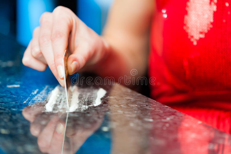 Young woman snorting cocaine in club or bar royalty free stock photos