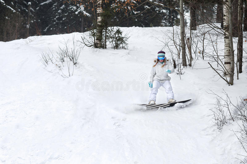 Young woman snowboarder in motion on snowboard in mountains royalty free stock images