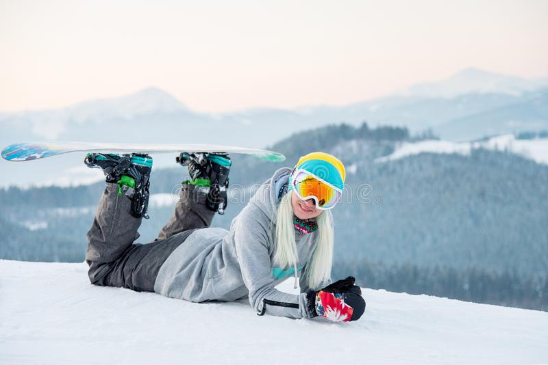 Young woman snowboarder relaxing outdoors lying on the snow smiling to the camera joyfully stock images