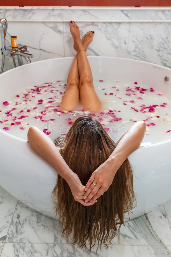 Young woman in spa enjoying bath with rose petals and relaxing stock images