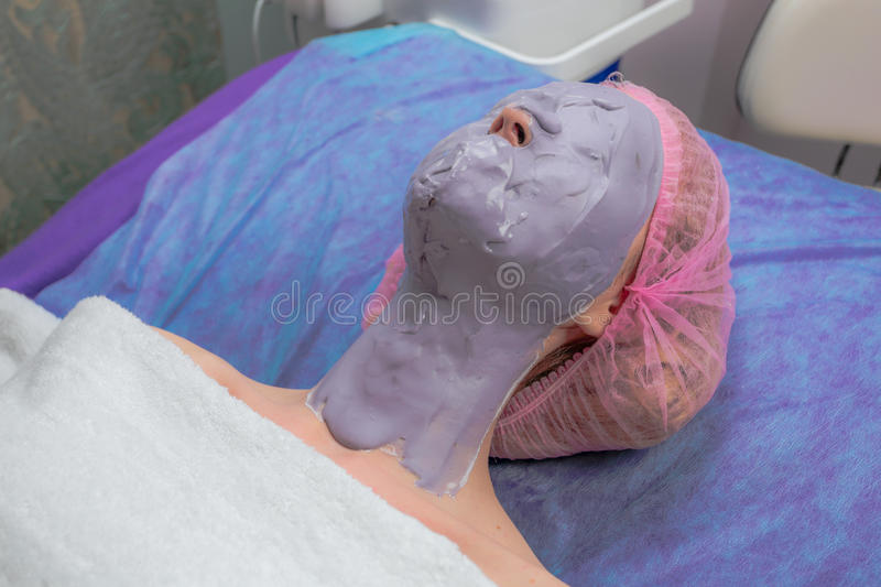 Young woman with spa facial mask on her face stock photography