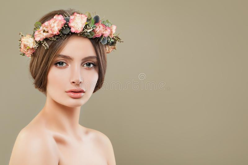 Young woman spa model with clear skin wearing flowers crown. Beautiful face closeup stock photo
