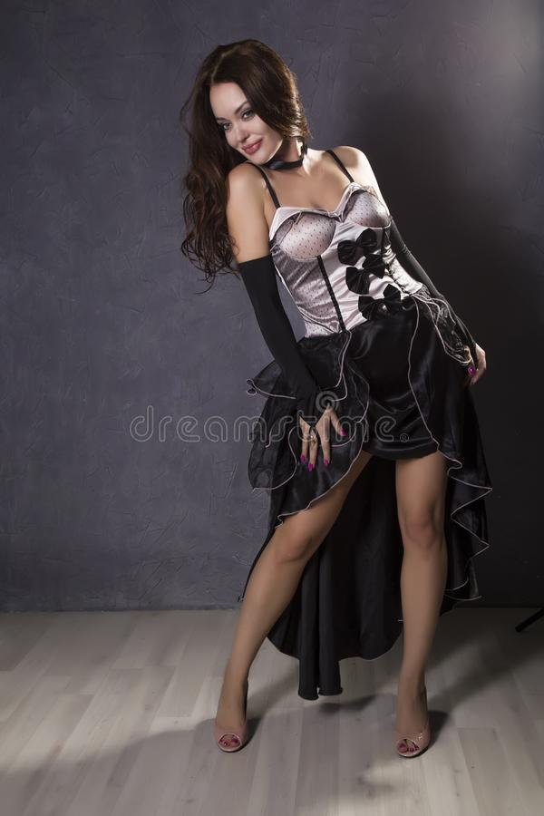 Young woman in a Spanish dress dancing on a gray background royalty free stock image