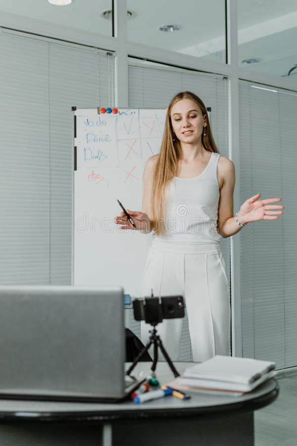 Young woman speaking in front of camera for vlog as blogger. Caucasian businesswoman working, recording video tutorial at office. royalty free stock images
