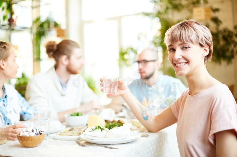 Young woman spending time in cafe with friends royalty free stock photo