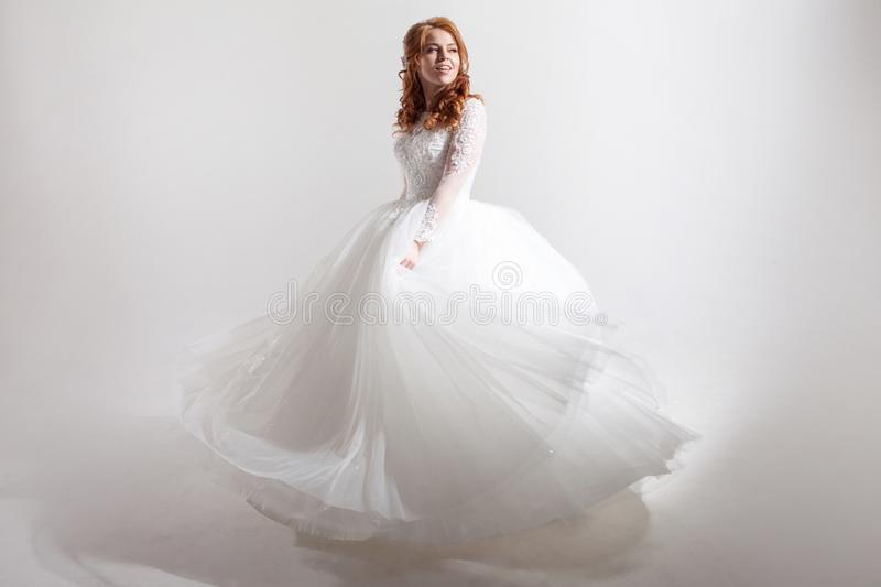Download Young Woman Spinning In A Curvy Wedding Dress. Woman Bride In Lavish Wedding Dress. Light Background. Stock Photo - Image of portrait, cheerful: 117564920
