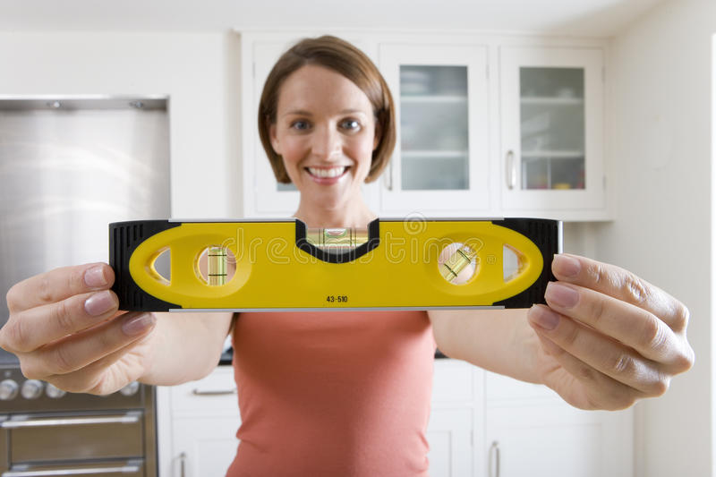 Young woman with spirit level in kitchen, smiling, close-up of hands royalty free stock photo
