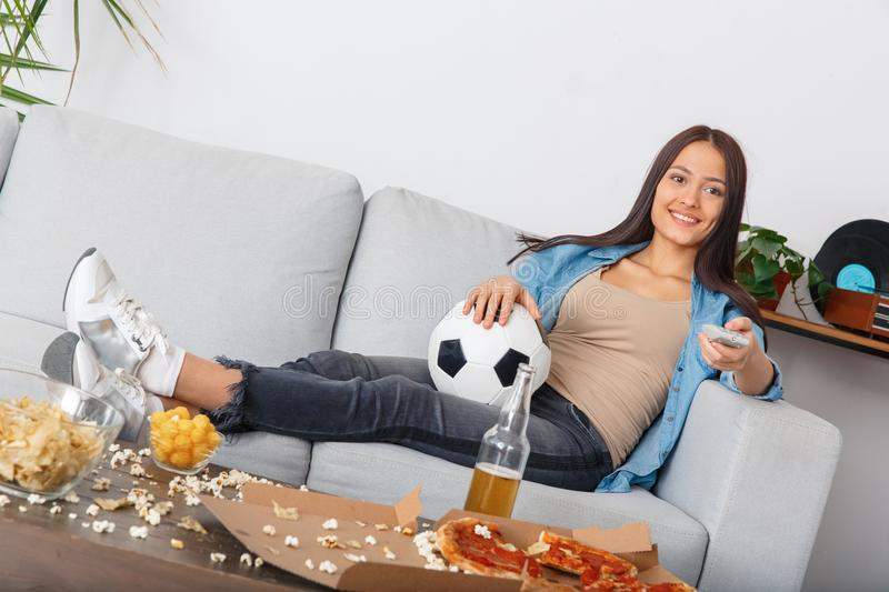 Young woman sport fan watching match changing volume with remote controller stock photo