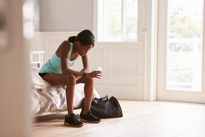 Young woman in sports clothes sitting at home drinking water stock photo