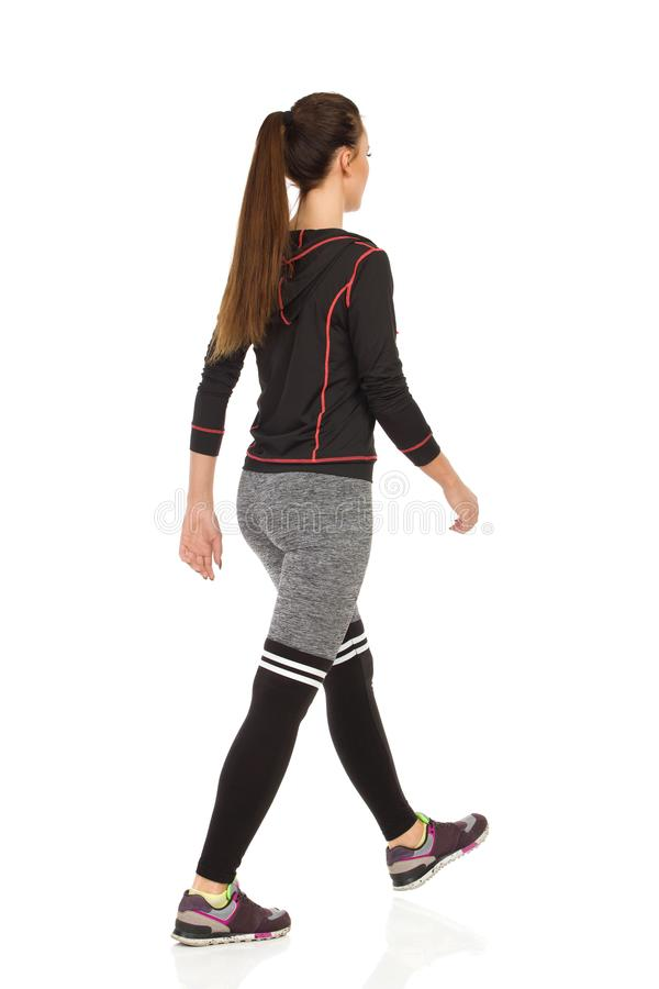 Young Woman In Sports Clothes Is Walking. Rear Side View. Full length studio shot isolated on white royalty free stock image
