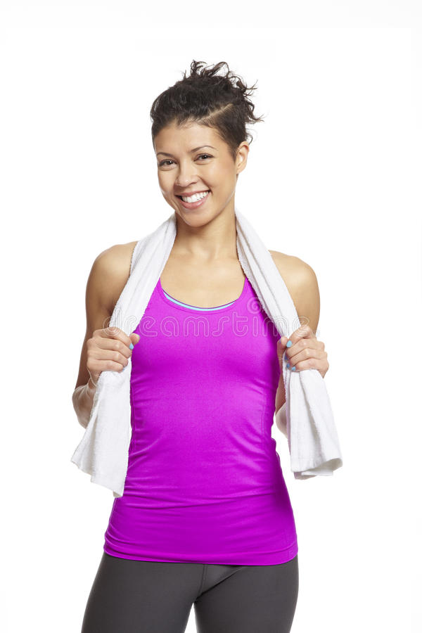 Young woman in sports outfit. With a towel smiling on white background stock photography