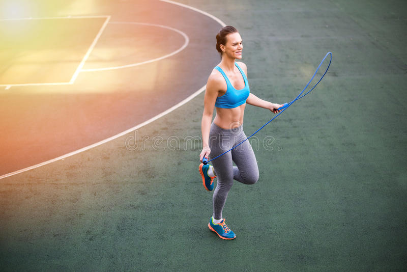 Young woman in sportswear exercising with skipping rope on stadium. Smiling young woman in sportswear exercising with skipping rope on stadium royalty free stock photo