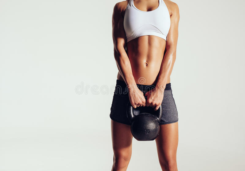 Young woman in sportswear holding a kettle bell. Cropped shot of young woman in sportswear holding a kettle bell. Strong fitness female exercising crossfit with stock image