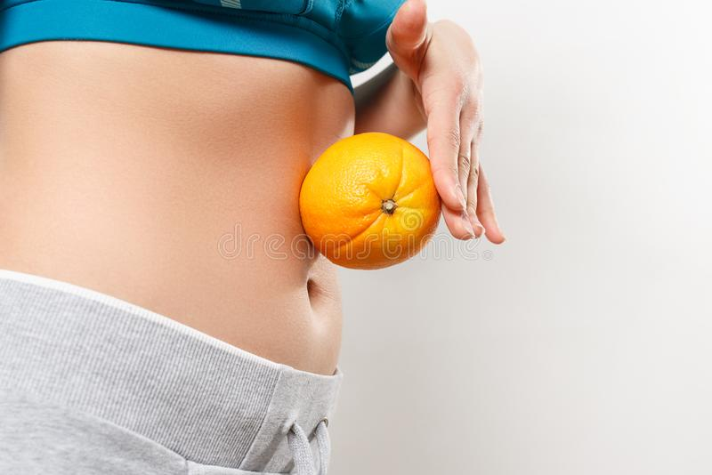 A young woman in sportswear holds an orange on her stomach royalty free stock photos