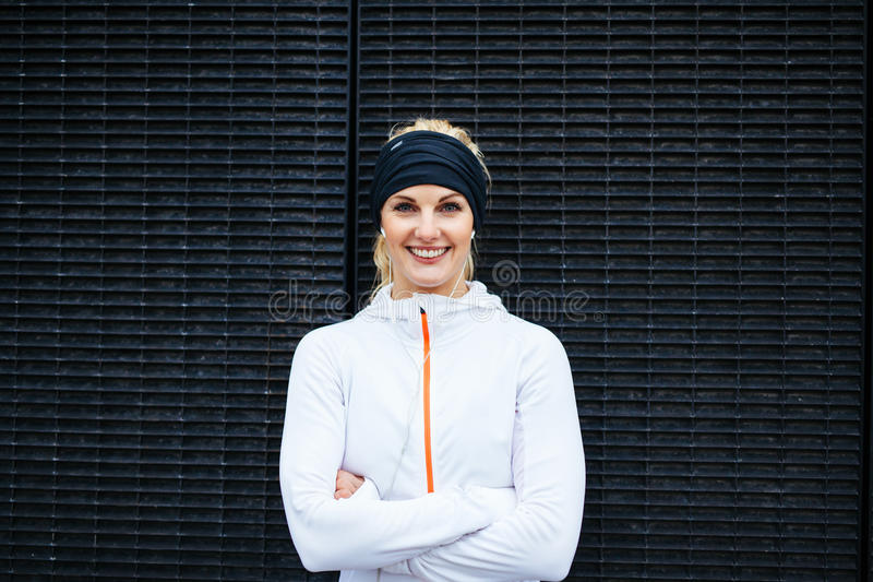Young woman in sportswear looking at camera smiling. Portrait of happy young woman in sportswear looking at camera smiling. Fitness female against dark wall royalty free stock photos