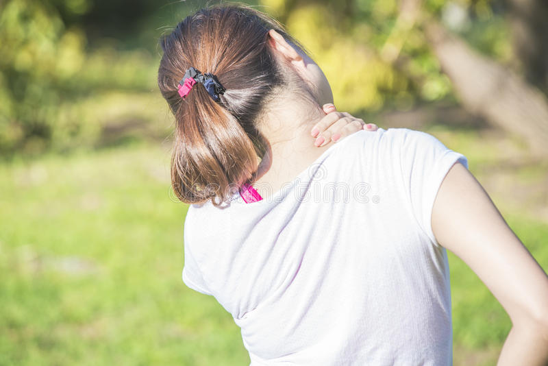 Young woman in sportswear touching her neck and lower back muscles by painful injury stock images