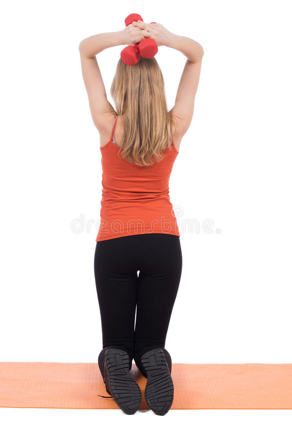 Young woman in sportswear training back with the red dumbbells. royalty free stock images