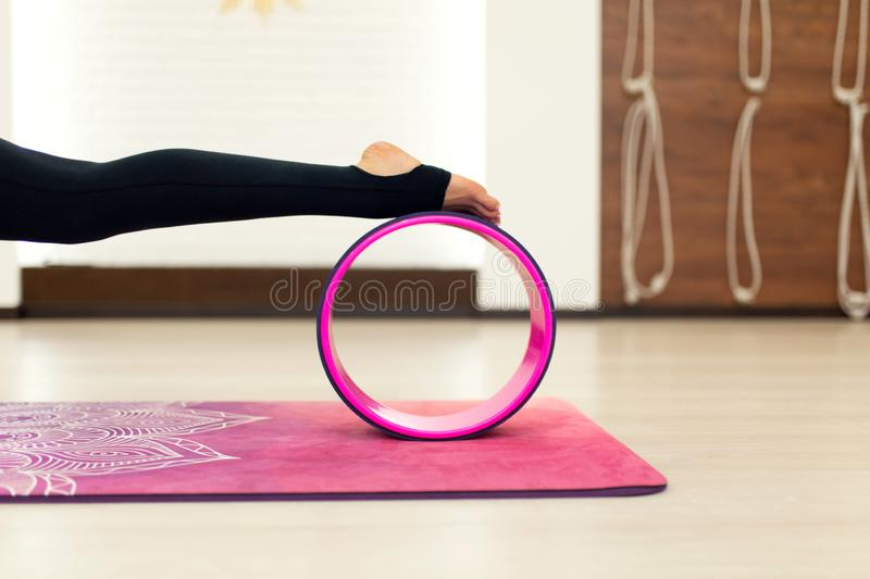 Young woman in a sportswear yoga exercises with a yoga wheel in the gym. Stretching and wellness lifestyle.  royalty free stock images