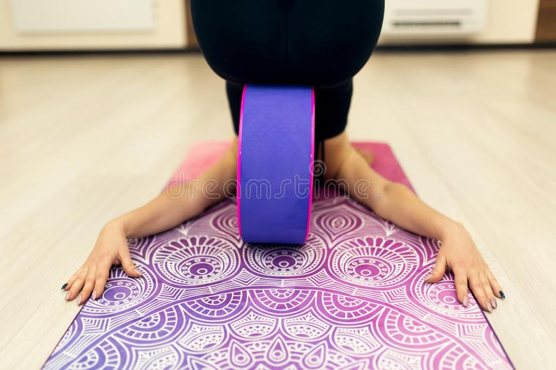 Young woman in a sportswear yoga exercises with a yoga wheel in the gym. Stretching and wellness lifestyle.  royalty free stock photos