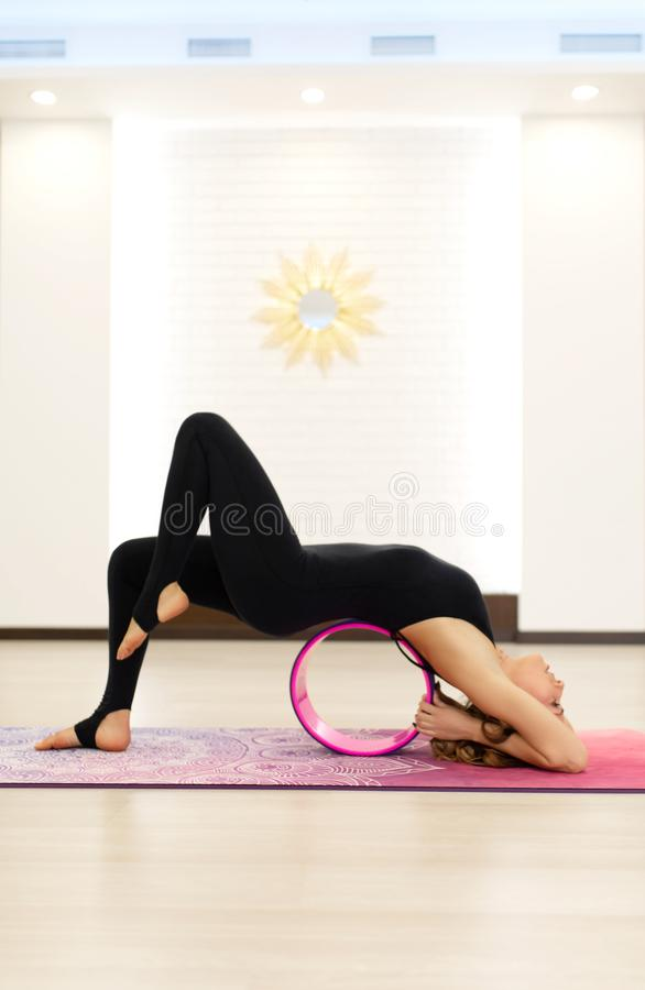 Young woman in a sportswear yoga exercises with a yoga wheel in the gym. Stretching and wellness lifestyle.  stock photography