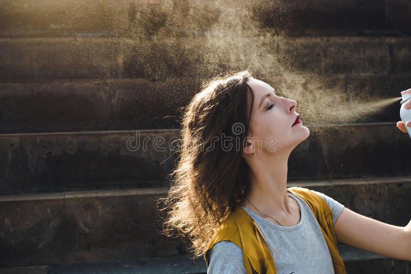 Young woman spraying face with thermal water. Enjoying, skin care concept. royalty free stock photo