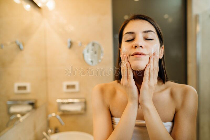 Young woman spreading hydration products,skincare routine at home.Daytime facial creme.Removing makeup.Spa day,having fun.Feminine royalty free stock image