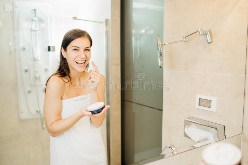 Young woman spreading hydration products,skincare routine at home.Daytime facial creme.Removing makeup.Spa day,having fun.Feminine royalty free stock photo