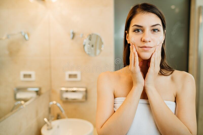 Young woman spreading hydration products,skincare routine at home.Daytime facial creme.Removing makeup.Spa day,having fun.Feminine stock images