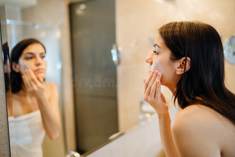 Young woman spreading hydration products,skincare routine at home.Daytime facial creme.Removing makeup.Spa day,having fun.Feminine stock photography
