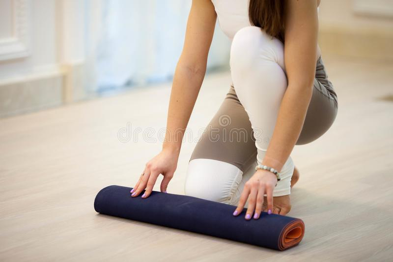 The young woman spreads a Mat for yoga royalty free stock images