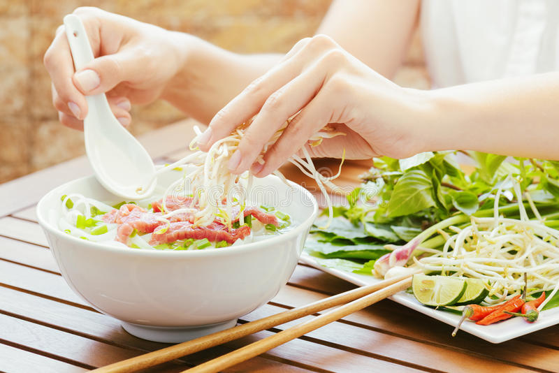 Young woman sprinkles sprouts to the Pho Bo in Vietnamese cafe stock photos