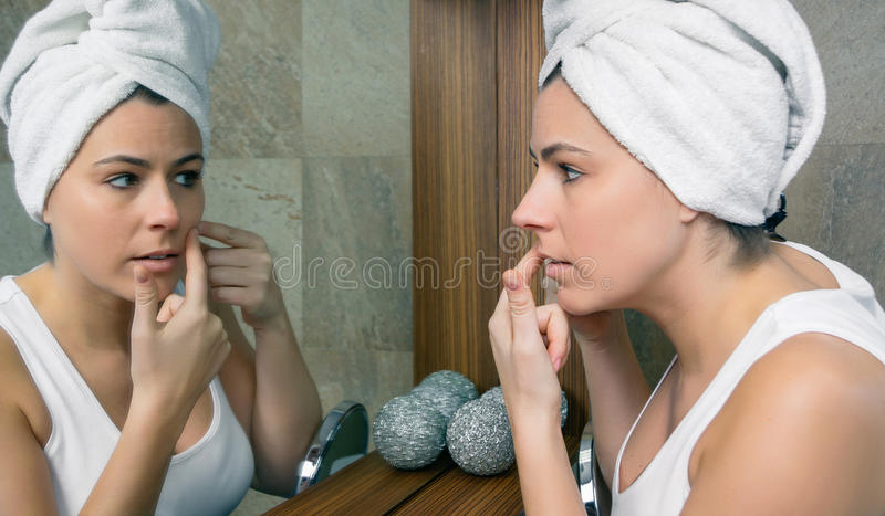 Young woman squeezing an acne pimple in mirror. Closeup of young woman with a towel over hair squeezing an acne pimple in her beautiful face in front of a mirror royalty free stock photos