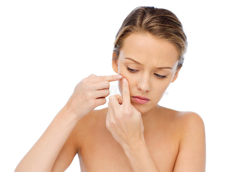 Young woman squeezing pimple on her face. Beauty, people, skincare and health concept - young woman squeezing pimple on her face royalty free stock photos