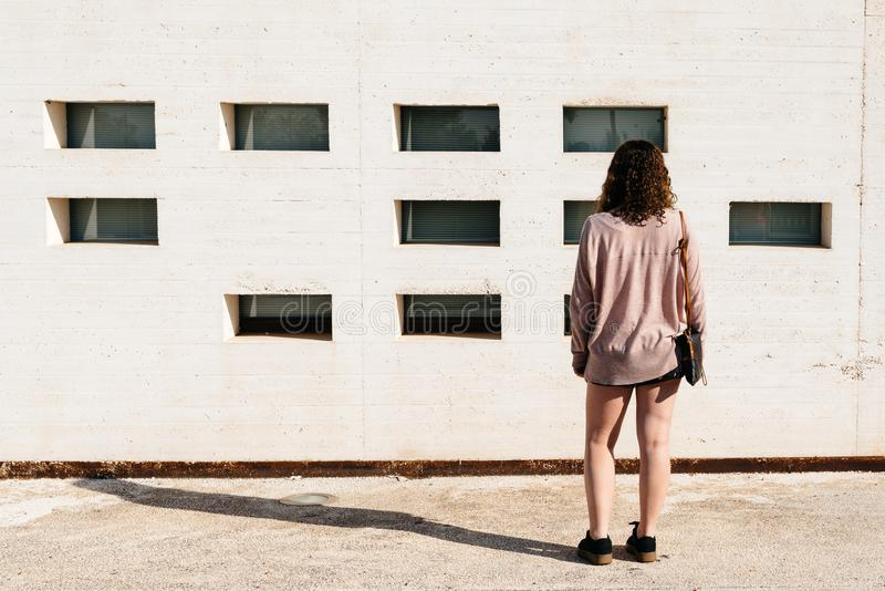 Young woman standing against white wall stock images
