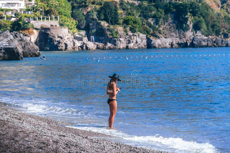 Young woman standing alone at beach and look at her phone. Concept good, bad signal stock image