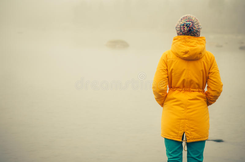 Young Woman standing alone outdoor Travel Lifestyle. And melancholy emotions concept winter foggy nature on background royalty free stock images