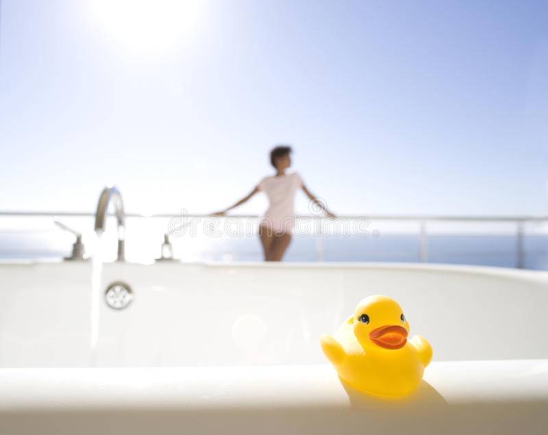 Young woman standing on balcony by sea, bath with rubber duck in foreground royalty free stock photography