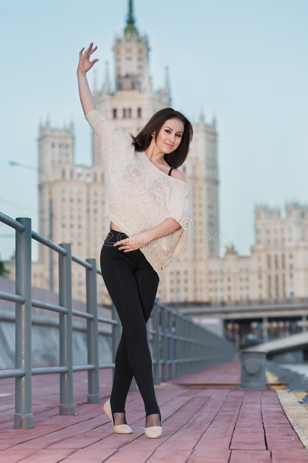 A young woman is standing in a ballet position on the waterfront stock image