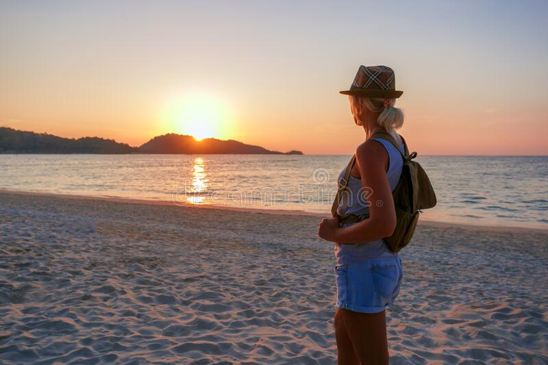 Young woman standing on the beach in sea and looking to sunset. She is enjoying serene ocean nature during travel holidays vacation outdoors royalty free stock photo