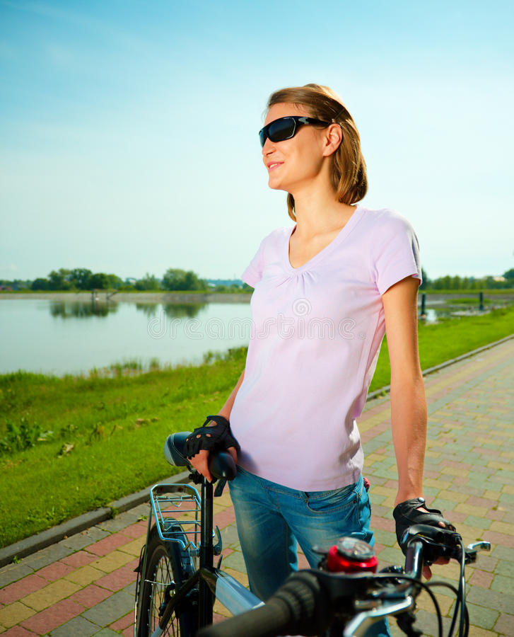 Young woman is standing behind bicycle. Young happy woman is standing behind bicycle, outdoor shoot stock photos