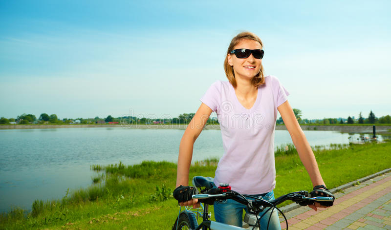 Young woman is standing behind bicycle. Young happy woman is standing behind bicycle, outdoor shoot stock photo