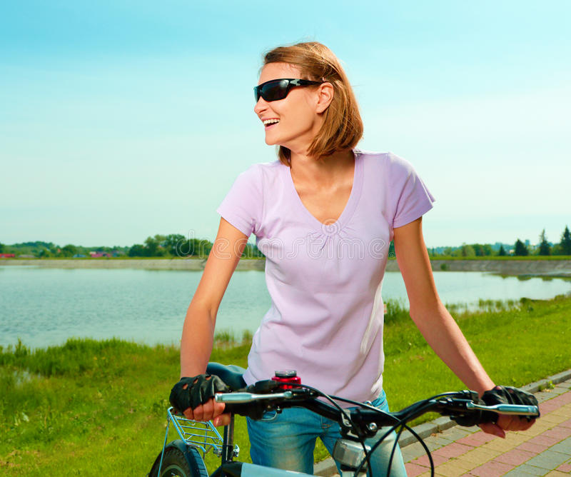 Young woman is standing behind bicycle. Young happy woman is standing behind bicycle, outdoor shoot stock image