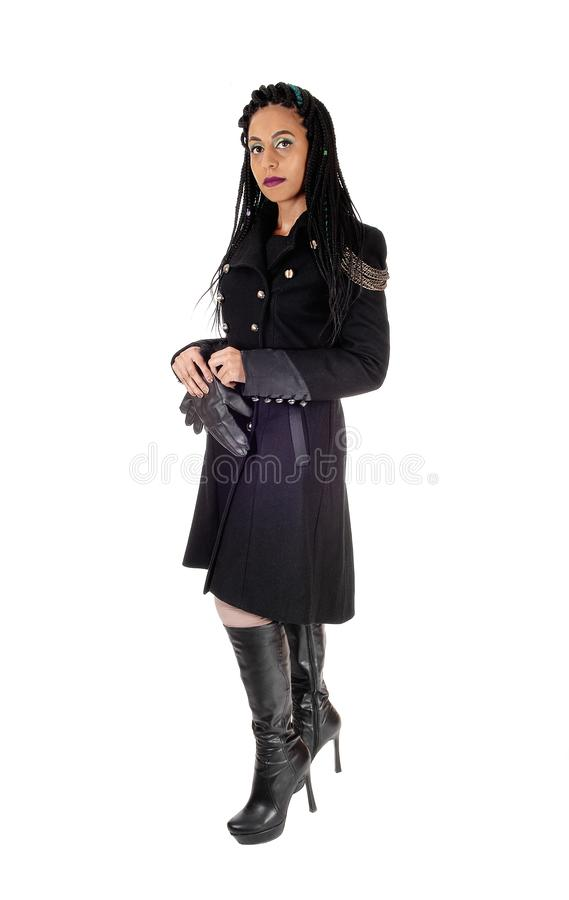 Young woman standing in black coat and boots royalty free stock images